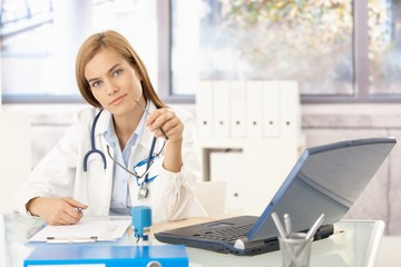 Attractive doctor writing report sitting at desk
