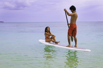 beachboy with girl in bikini on paddle board in hawaii