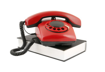 Retro rotary telephone on black book isolated