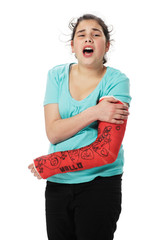 Girl with red plaster cast has pain and holds her broken arm