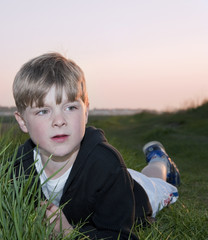Portrait of young boy backlit against beautiful setting sun