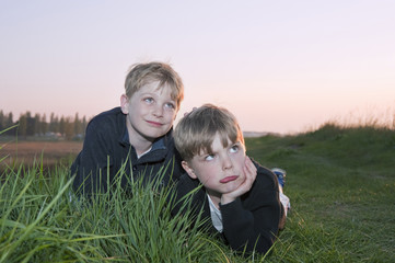 Two brothers play in front of camera in field at sunset with fun