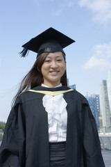 Smiling asian lady graduate in city