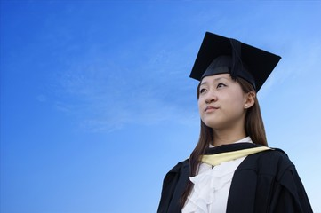 Serious female asian graduate with sky background