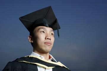 Serious asian male graduate with dark blue sky
