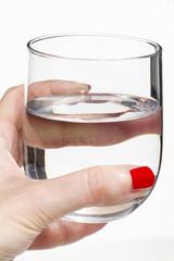 Mano di donna che tiene un bicchiere d'acqua