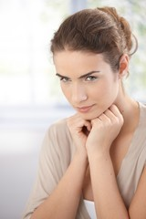 Portrait of attractive thinking woman in beige