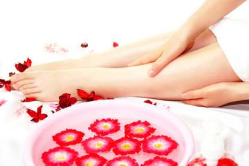 花と女性の足とエステマッサージ