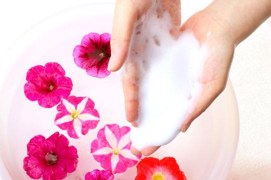 花と美容アロマ女性の手と水の容器