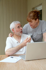 Senior couple checking medical information on internet