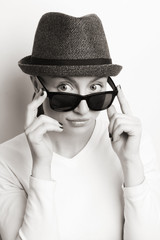 Retro photo of a girl in sunglasses and an old hat