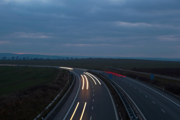 Cars moving fast on a night highway (motion blurred image)