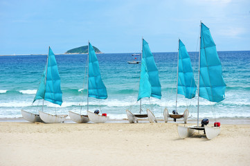 Blue Sails Of Wind Surf Crafts  At The Beach