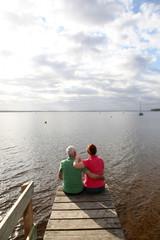 Back view of senior couple sitting on a pontoon
