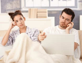 Young couple in bed man working woman bored