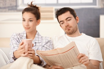 Young couple in bed man reading woman drinking tea