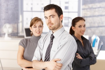 Young colleagues standing in office arms crossed