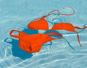 Orange bikini in clean water. Swim suit in turquoise pool.