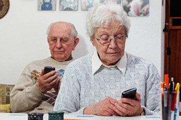 senior couple with smartphones