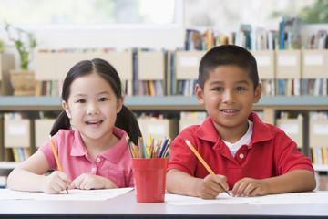 Kindergarten children sitting at desk and writing in classroom