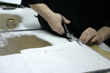 Frau schneidet Stoff mit Schneiderschere