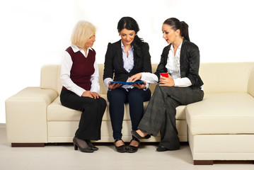 Three business women discussion on sofa