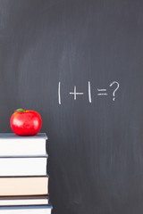 """Stack of books with a red apple and a blackboard with """"1+1=?"""" wr"""