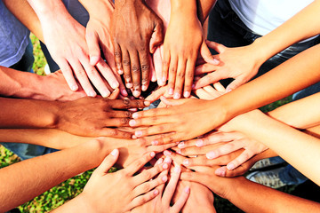Obraz many hands together: group of people joining hands - fototapety do salonu