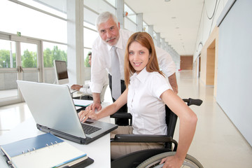 Woman in wheelchair with trainer in office