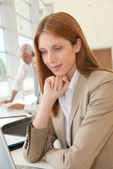Smiling businesswoman in front of laptop