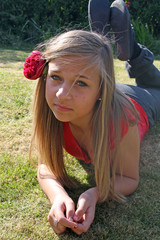 blonde teenage girl with red flower in her hair