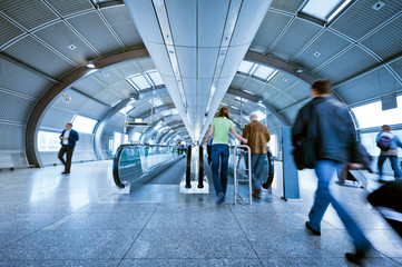blurred passengers on indoor moving walkway