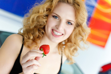 Young woman with strawberry near New car