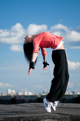 woman dancing hip hop over blue sky