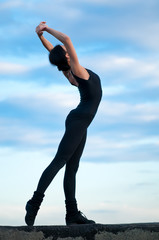 dancing woman over blue sky. Yoga