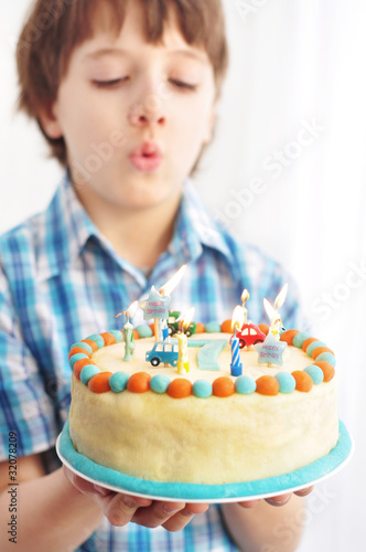 7 Year Old Boy Blowing Candles On His Birthday Cake