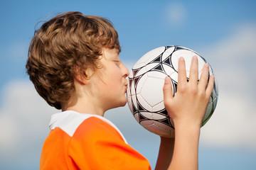 glücklicher junge küsst fußball