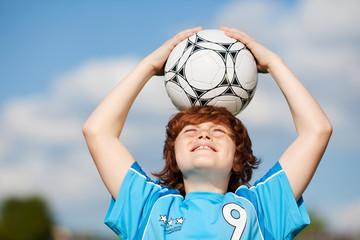 junge hält fußball auf dem kopf