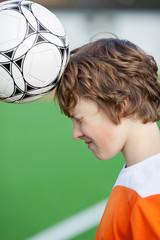 junger fußballer macht kopfball