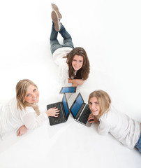 Aerial view of three smiling girls with computer