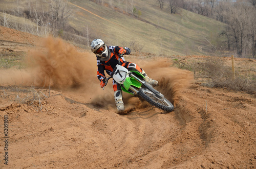 Fototapete Motocross rider with a strong slope turns sharply