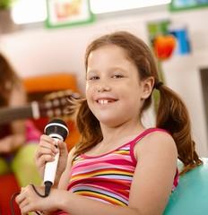 Happy schoolgirl with microphone