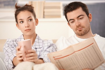 Young couple in bed man reading woman bored