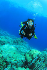Young Woman Scuba Diving over coral reef
