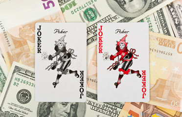 Two playing card jokers over heap of money