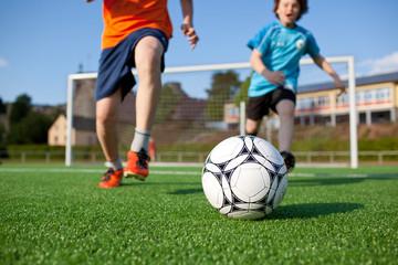 zwei jungs spielen fußball