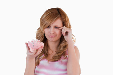 Blond-haired woman crying while holding her broken piggybank