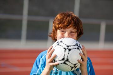 rothaariger junge mit fußball