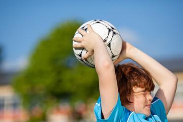 junger fußballspieler beim einwurf