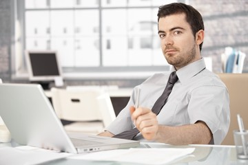 Young man sitting at desk using laptop